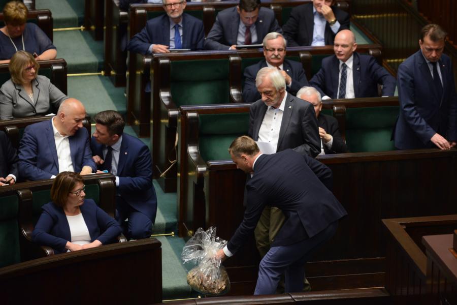 Poseł PO Sławomir Nitras (P) z workiem trocin, który wręczył politykom PiS w Sejmie