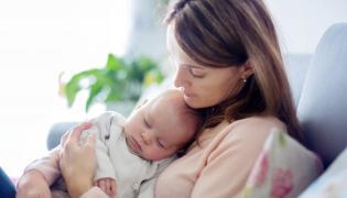 Młoda kobieta z niemowlakiem na rękach