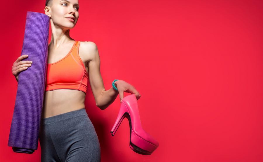 Kobieta idzie na fitness, ze szpilkami w ręku