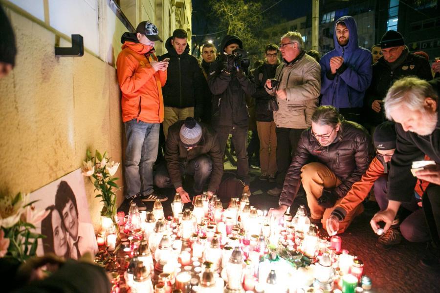 Świece zapalane przy ścianie domu, w którym mieszkał Kuciak