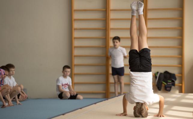 Lekcja WF, ćwiczenia gimnastyczne, dziecko stoi na głowie