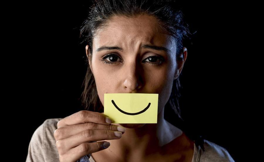 Kobieta z przyklejonym uśmiechem