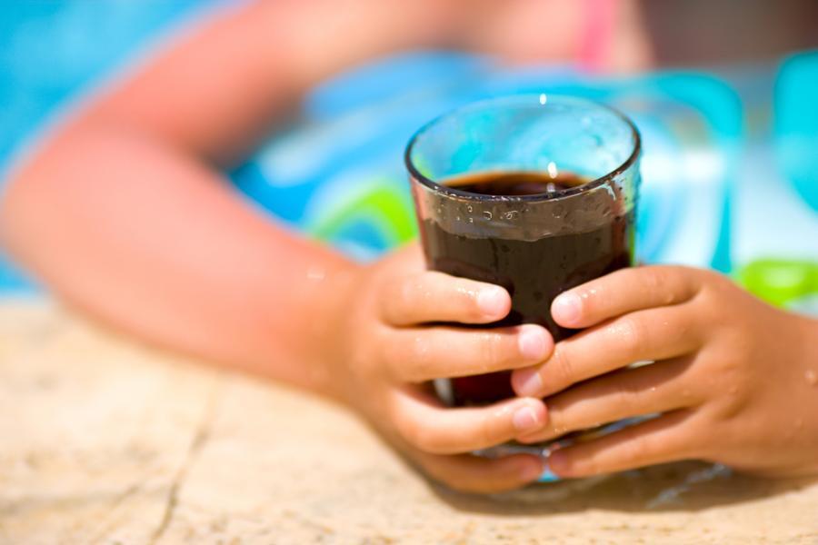 Dziecko trzymające szlankę z coca-colą