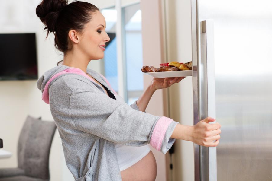 Kobieta w ciąży wyjmująca jedzenie z lodówki