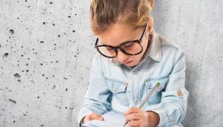 Mała dziewczynka pisze w zeszycie
