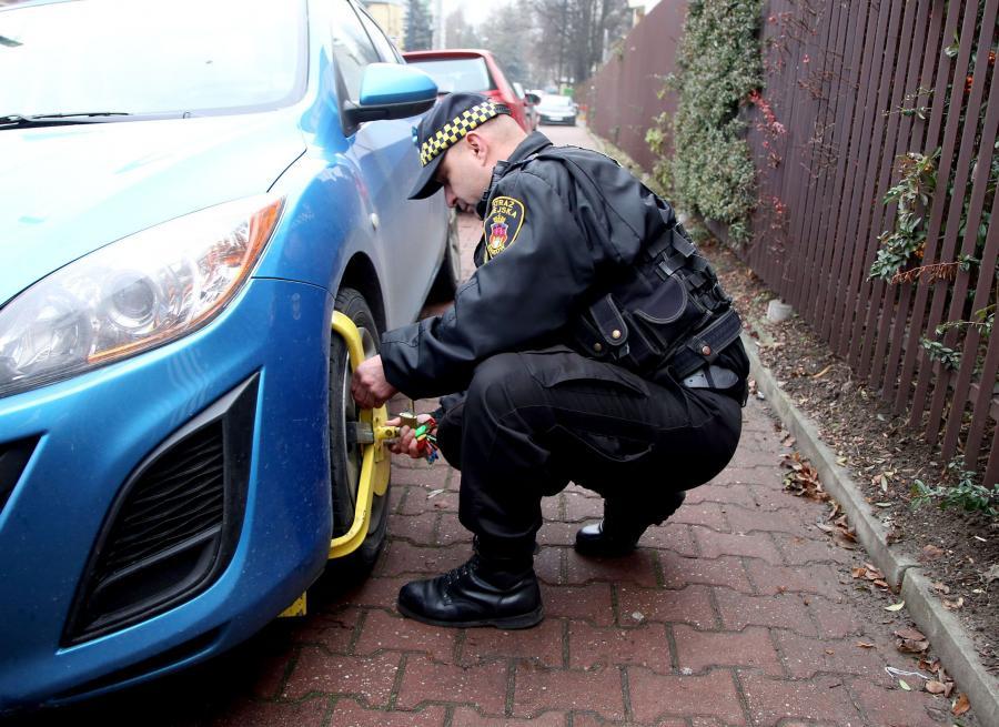 Straż miejska zakłada blokadę na źle zaparkowany samochód na ulicy Turystycznej w Krakowie. W tle volkswagen golf prezydenta Andrzeja Dudy