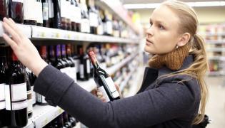 Kobieta wybiera wino w sklepie z alkoholem